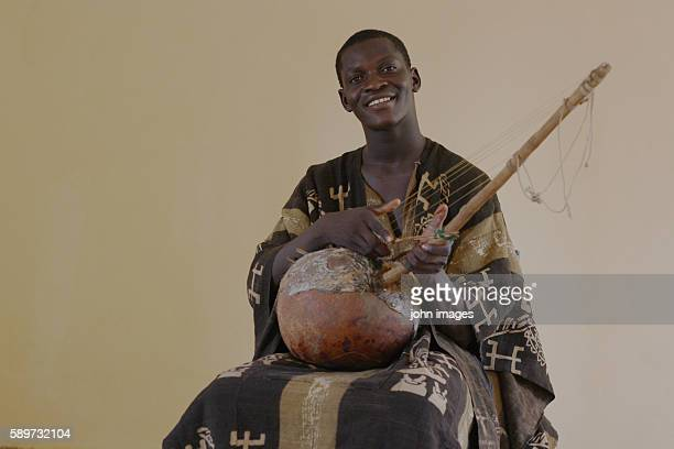 A man and held bogolan and Musical instrument