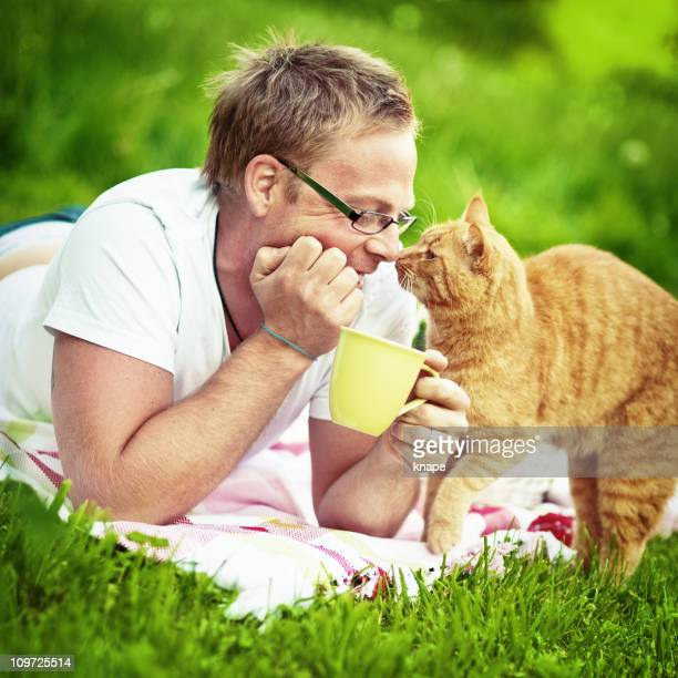 Man and his cat lying on the lawn