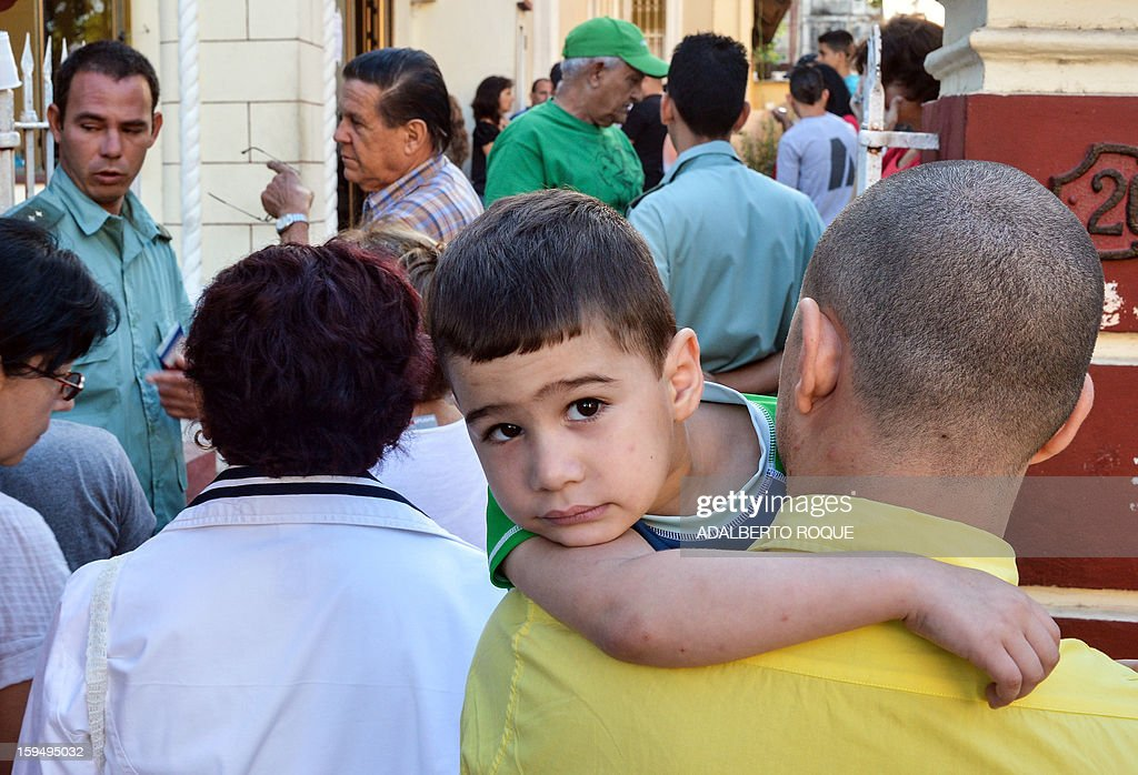A man and his child queues outside a Migration Office to request new passports, on January 14, 2013 in Havana. A law allowing Cubans to travel abroad without special exit visas took effect on the communist-ruled island for the first time in half a century. The measure does away with the exit visas that have kept most Cubans from ever traveling abroad.