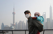 A man and his child wear masks as they visit The Bund on December 25 2013 in Shanghai China Heavy smog covered many parts of China on Christmas Eve...