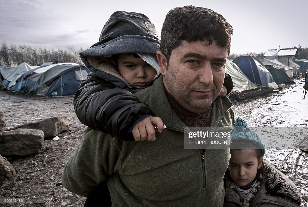 A man and his children from Iraq poses in the so-called 'Jungle' migrant camp in Gande-Synthe where 2,500 refugees from Kurdistan, Iraq and Syria live on February 11, 2016 in Grande-Synthe near the city of Dunkirk, northern France. / AFP / PHILIPPE HUGUEN