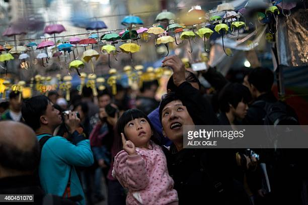 A man and his daughter pose for photos next to an installation of paper umbrellas symbols of the prodemocracy protests in Hong Kong in the Causeway...