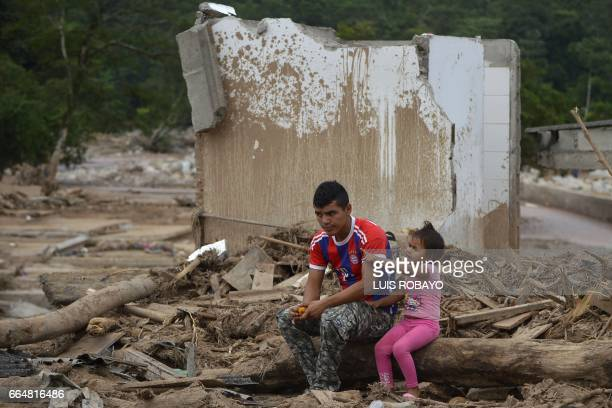 A man and his daughter remain amid rubble in Mocoa Putumayo department Colombia on April 4 2017 Meanwhile looting has become a problem in some areas...