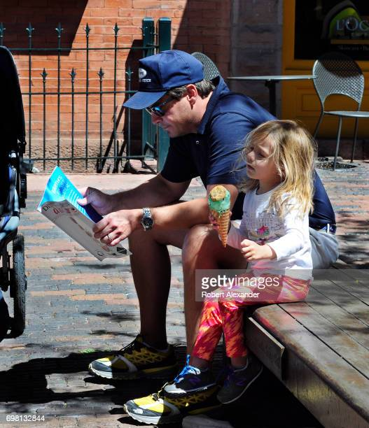 A man and his daughter visiting Aspen Colorado relax on a bench with a tourist magazine and an ice cream cone