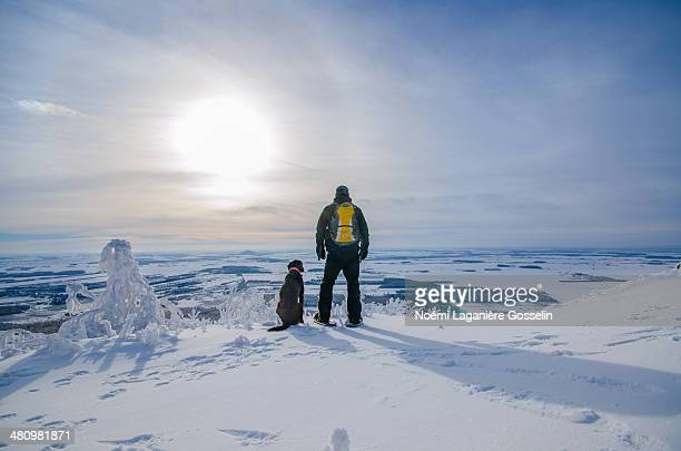 A man and his dog admiring the winter landscape