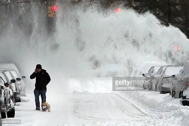 A man and his dog contend with blowing snow in Brooklyn following a snow storm that left up to 8 inches of snow on January 3 2014 in New York United...