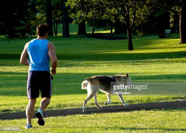 Man and his Dog jogging in a park.