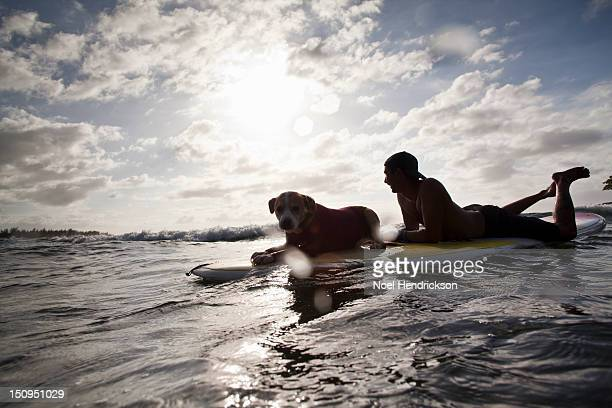 A man and his dog lay on a surfboard