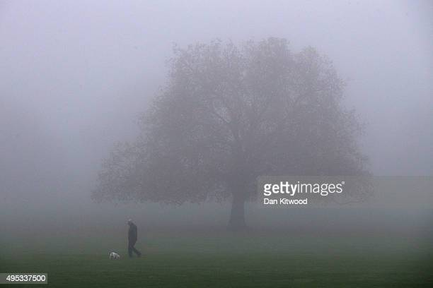 A man and his dog walk through a Peckham park in thick fog on November 2 2015 in London England Thick fog has covered much of the UK causing travel...