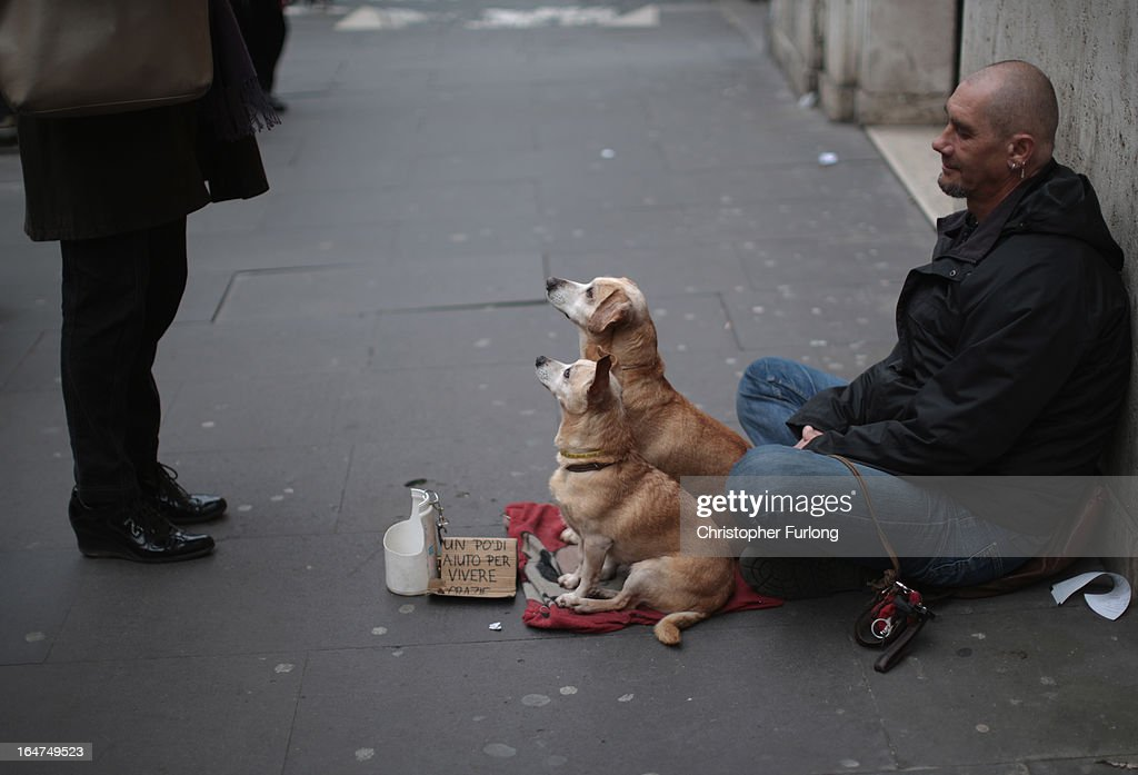 A man and his dogs beg for loose change in a street on March 27, 2013 in Rome, Italy. Recently elected Pope Francis declared that in his papalcy the catholic church would be a 'Church for the poor.'