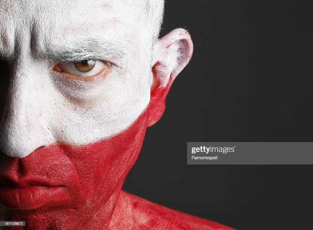 Hombre y su cara pintada con la bandera de Polonia : Foto de stock