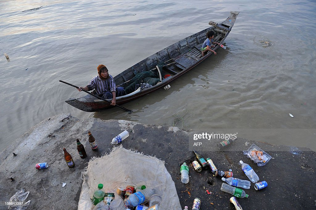 A man and his son collect beer bottles that were tossed away after a New Year's countdown party for 2013 at the Yangon jetty on January 1, 2013. An estimated 50,000 flocked to Yangon's revered golden Shwedagon Pagoda for the city's first public New Year countdown and fireworks display, seen as further evidence of opening up after decades of military rule. AFP PHOTO / Ye Aung Thu