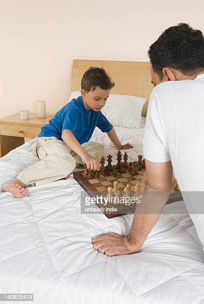 Man and his son playing chess on the bed