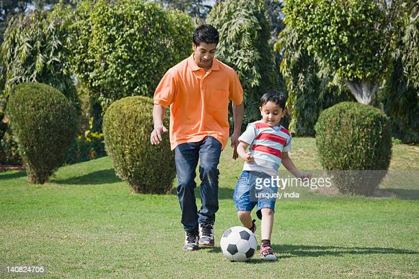 Man and his son playing with a soccer ball, Gurgaon, Haryana, India