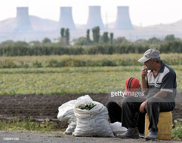A man and his son sell cucumbers on September 26 2010 in the vicinity of the Metzamor nuclear power station outside Yerevan The enormous cooling...