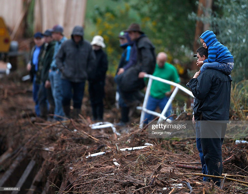 A man and his son stand on a debris pile watching construction equipment remove flood debris from Short Creek as it crosses Central Street on...