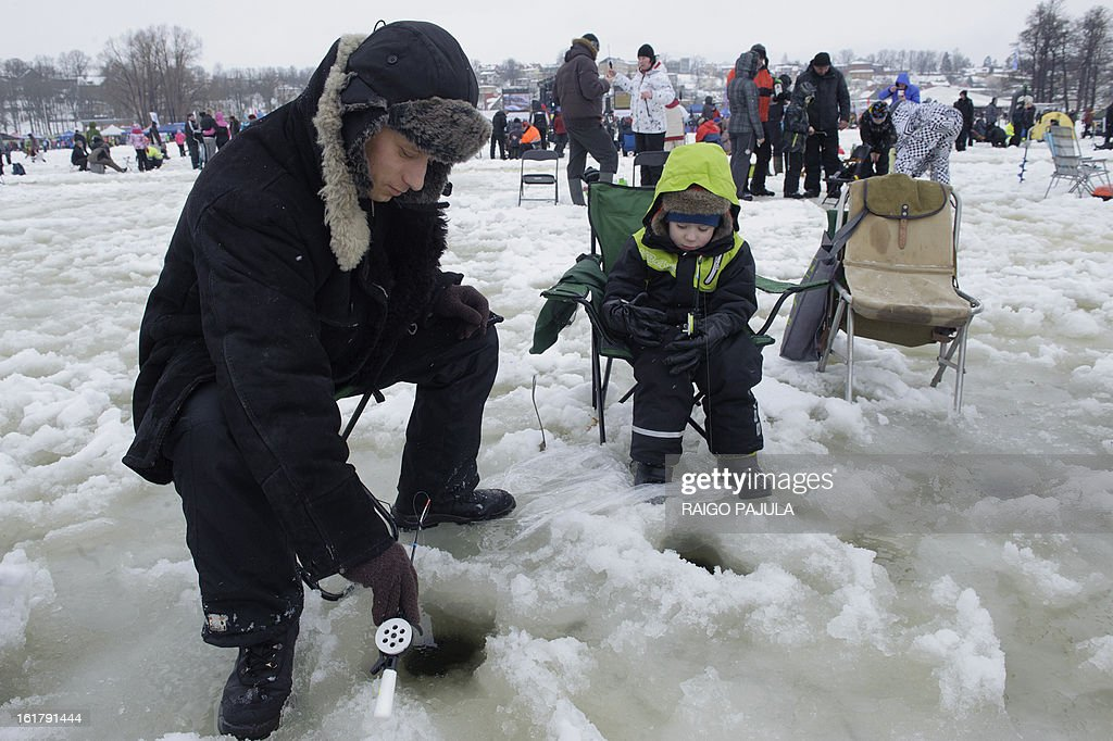 STORY - A man and his son take part in a fishing event on the frozen lake Viljandi in Viljandi, Estonia on February 16, 2013. More than 8,000 participants from different countries arrived for the fishing event.