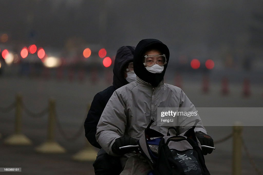 A man and his son wearing the mask ride the electric bicycle during severe pollution on January 30, 2013 in Beijing, China. The fourth round of heavy smog to hit Beijing in one month has sent more people to the hospital with respiratory illnesses and prompted calls for legislation to curb pollution. The haze choking many Chinese cities covers a total area of 1.3 million square kilometers, the China's Ministry of Environmental Protection said Tuesday.