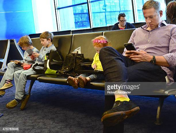 A man and his three children use their smartphones tablets and other mobile devices as they wait for their flight in the boarding gate area at...