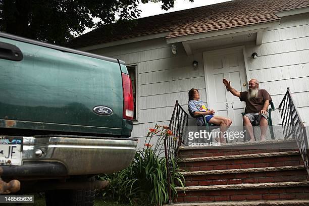 A man and his wife both of whom are on disability sit on the porch of their home on June 19 2012 in Deposit New York The Southern Tier of New York an...