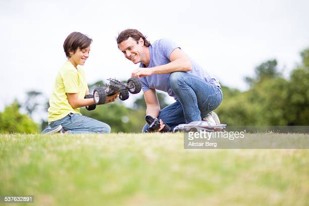 Man and hs son playing with car