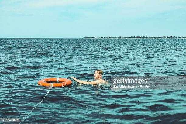 Man And Life Ring In Sea Against Sky