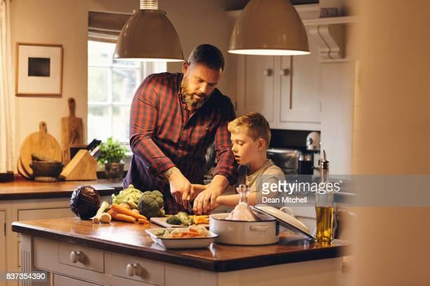 Man and little boy cutting fresh vegetables in kitchen