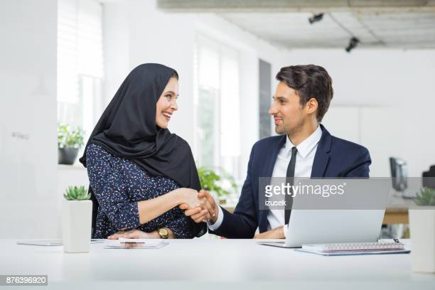 Man and muslim woman shaking hands in office