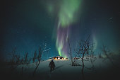 A figure walks towards a cabin under the beautiful Northern lights in the night sky above Riksgransen, Sweden.