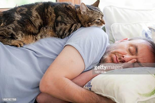 Homme et le cat: Confiance en/chambre à coucher