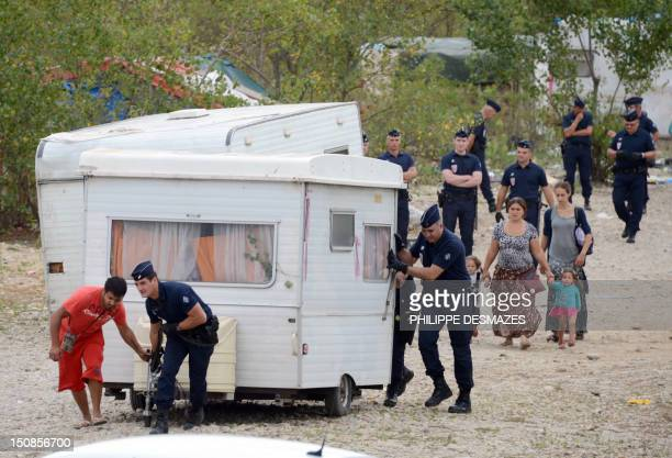 A man and police officers move a caravan while members from the Roma community are expelled from a camp by French police on August 28 in SaintPriest...