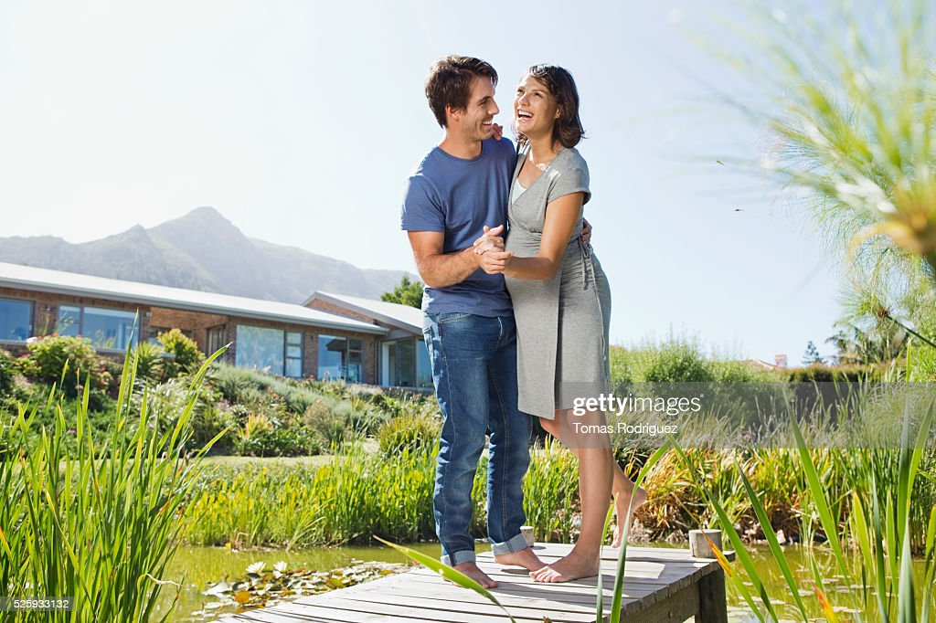 Man and pregnant woman dancing on jetty : Stock Photo