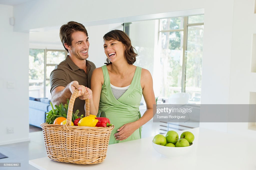 Man and pregnant woman holding basket with vegetables in kitchen : Stock Photo