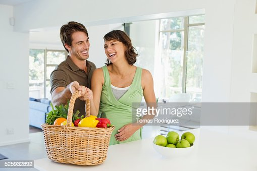 Man and pregnant woman holding basket with vegetables in kitchen : Stockfoto