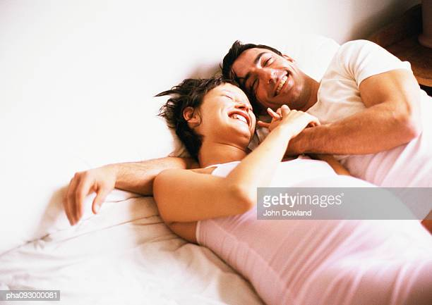 Man and pregnant woman side by side on bed