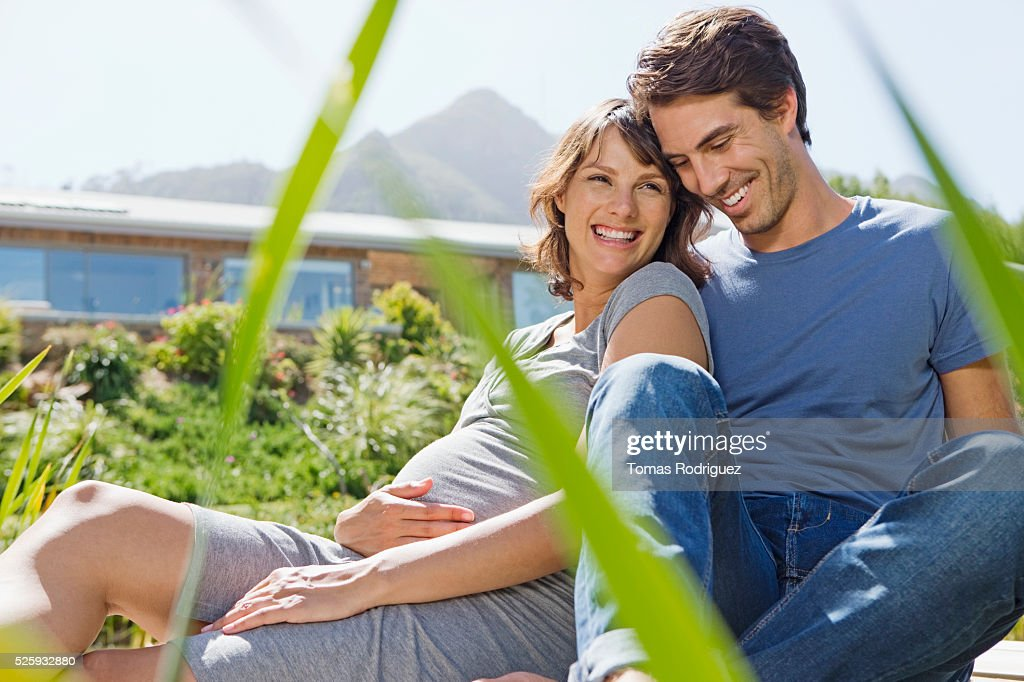 Man and pregnant woman sitting on jetty : Photo