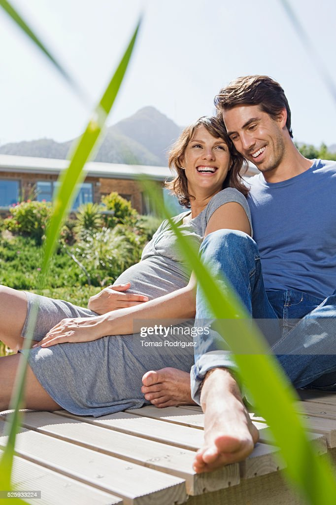 Man and pregnant woman sitting on jetty : Stock Photo