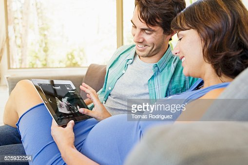 Man and pregnant woman sitting on sofa and using digital tablet : Foto stock