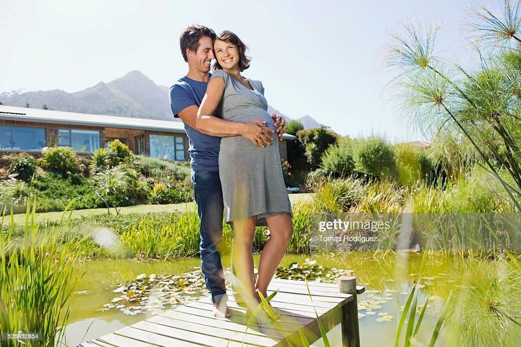 Man and pregnant woman standing on jetty : Stock Photo