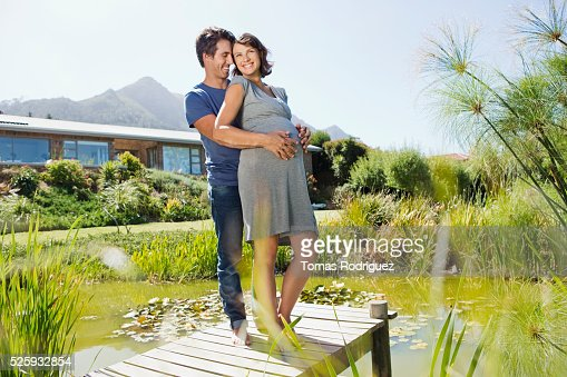 Man and pregnant woman standing on jetty : Stock-Foto