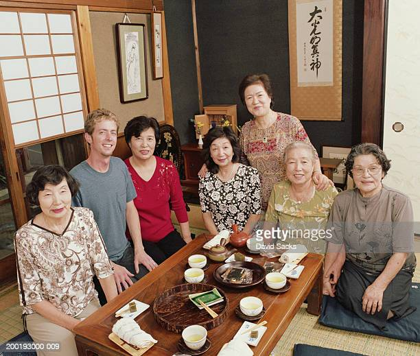 Man and senior women sitting around table, smiling, portrait