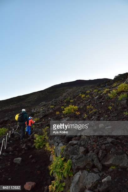 Man and son climbing Mt.Fuji