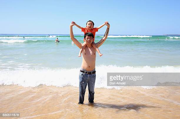 A man and son from Beijing China play in the shallow surf at Bondi Beach on December 25 2016 in Sydney Australia Bondi Beach is a popular tourist...