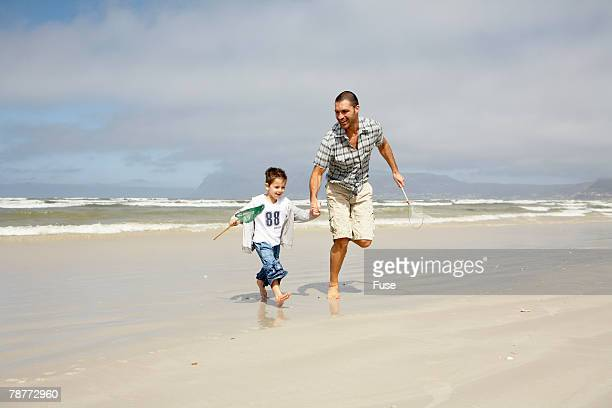 Man and Son with Fishing Nets Running on Beach