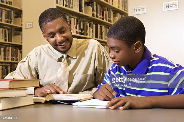 Man and teenage boy in library