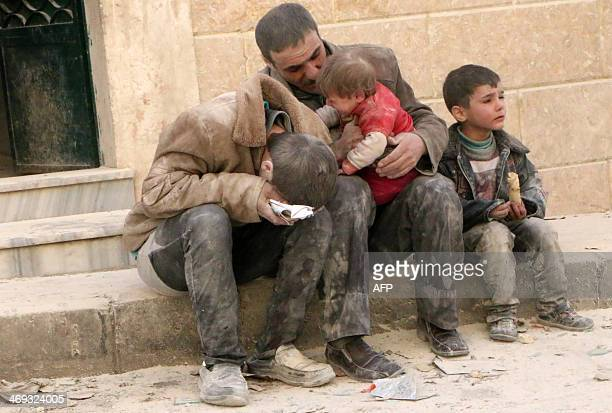 A man and three boys covered with dust sit in a state of shock following a reported air strike attack by government forces on the Hanano district of...