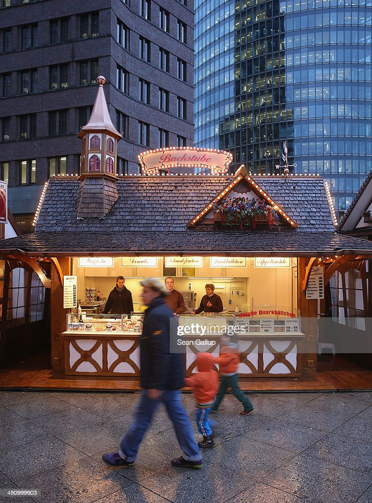 A man and two children walk past a Christmas market on Potsdamer Platz on November 20, 2013 in Berlin, Germany. Berlin, with still over a month to go, is preparing for Christmas.