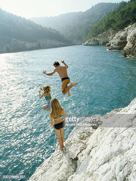 Man and two girls (7-9) jumping off cliff into sea, rear view