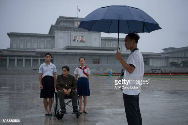 A man and two girls wait to have their photo taken as they pay their respects to late North Korean leaders Kim IlSung and Kim JongIl outside Kumsusan...