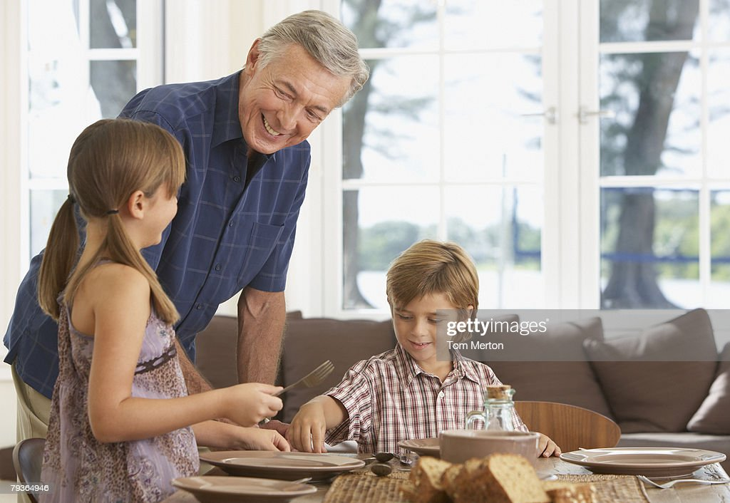 Man and two kids in dining room setting table : Stock Photo